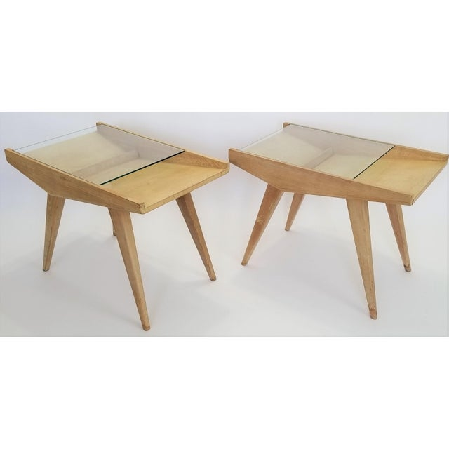 Offering a rare and stunningly dynamic pair of blond wood magazine end tables, circa 1950s...signed. These magnificent...