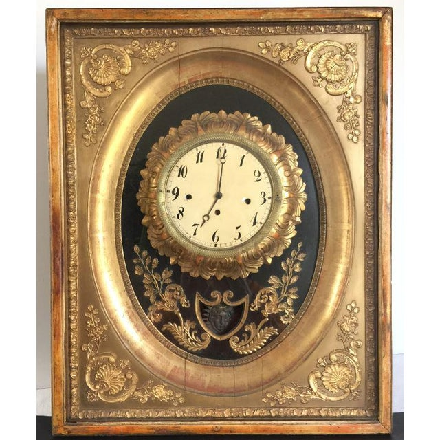 This is an antique French giltwood and brass clock mounted in a shadow box. It is probably mid-to-late 19th century. It...