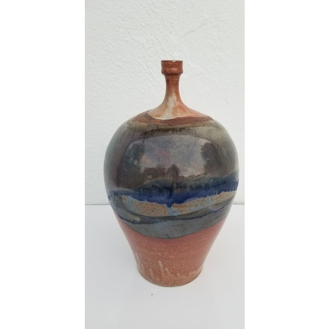 A vintage art studio pottery decorative bud vase. Features beautiful expressionist abstract colors with a glaze texture....