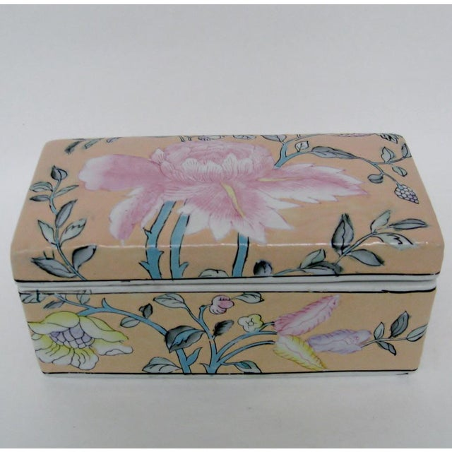 Chinese hand-painted porcelain lidded box finished in apricot glaze with pink lotus blossom and assorted flowers. Maker's...