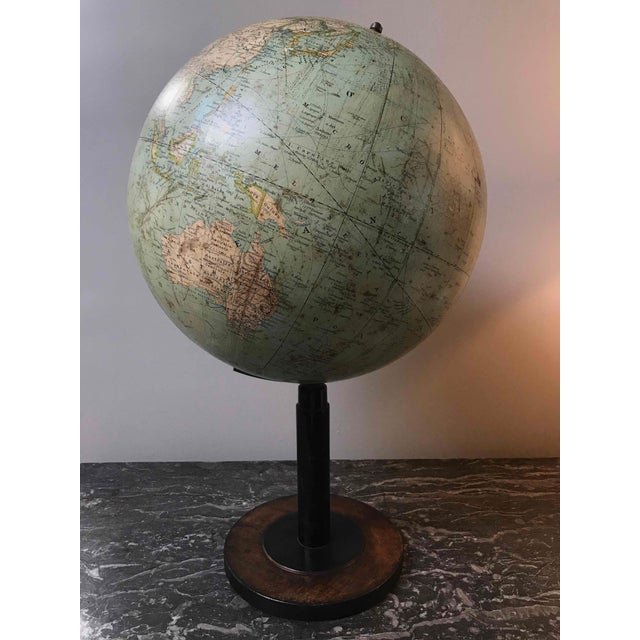 Early 20th century tall globe on black wood stand. Made in Italy.