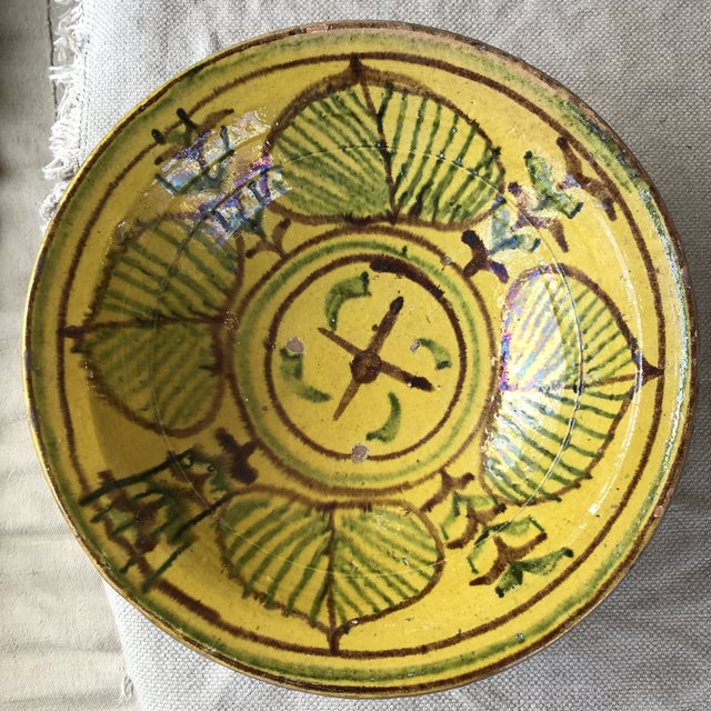 Gorgeous hand painted bowl in a vibrant yellow and green glaze depicting aspen leaves and wheat motifs.