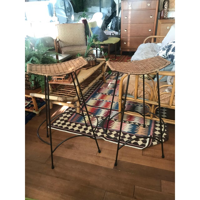 Pair of wrought iron stools with woven rattan seats. The stools are stackable.