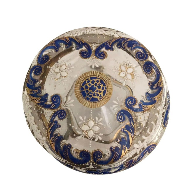 An antique round dresser box from France. Clear glass with blue, white and gold enamel. Circa 1900.