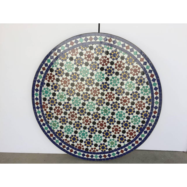 Moroccan round mosaic tile table delicately handcrafted by expert artisans in Fez, Morocco, using reclaimed old glazed...