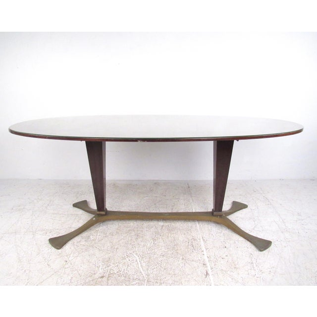This stylish 1950s Italian dining table features a unique brass finish base with tapered pedestals, as well as a glass top...