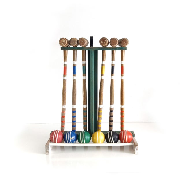 A green and white wooden stand loaded with six croquet mallets and balls make up this vintage croquet set. There is...