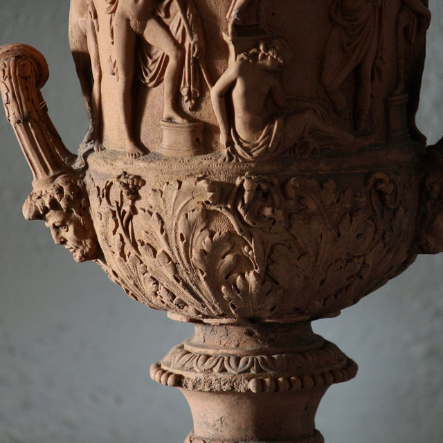 Twin handled terracotta garden urns decorated with classical figures.