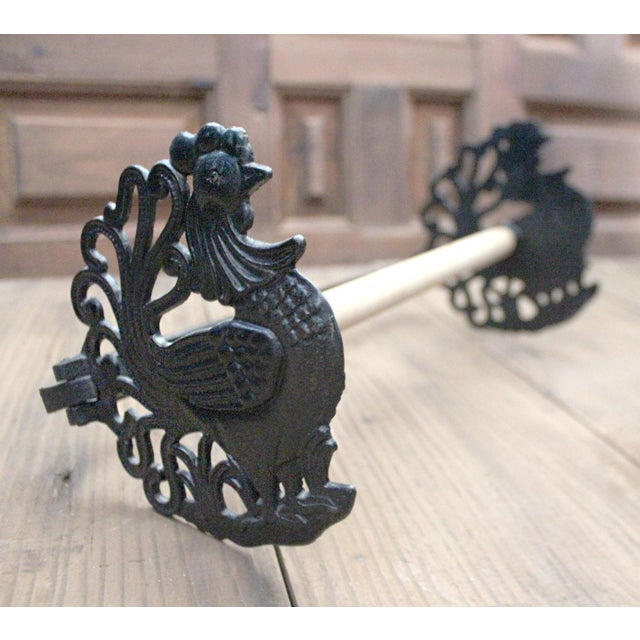 Delightful pair of roosters, adorn the sides of towel holder. The cast iron birds have curled feathers and a bold texture...