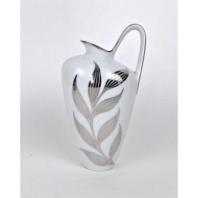 A sleek Mid-Century white porcelain pitcher decorated with silver metal overlay from Heinrich & Co. (H & Co.) of Selb...