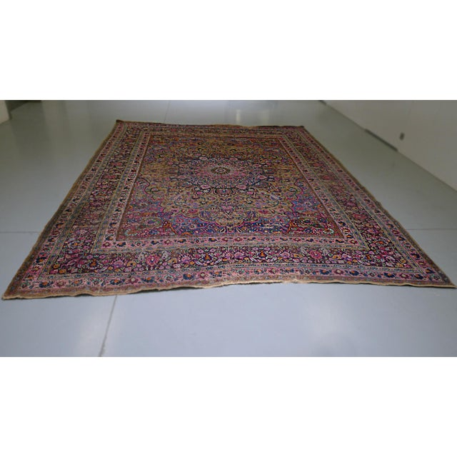 This Kerman rug was handwoven in the 1920s. It is richly colored, the dye varying in intensity and wear, adding to the...