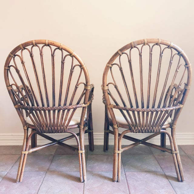 Pair of vintage rattan, fan back chairs, with cream colored fabric seats. Excellent condition!