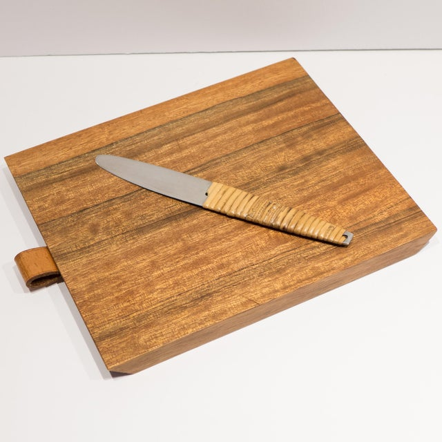 Wooden cutting board in a trapezoidal shape with a leather loop holding a cane-wrapped stainless steel knife. The knife is...