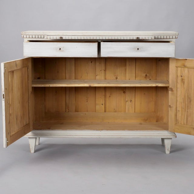 Swedish cabinet is painted in ecru with contrasting white diamond panels and drawer fronts and carved details, circa...