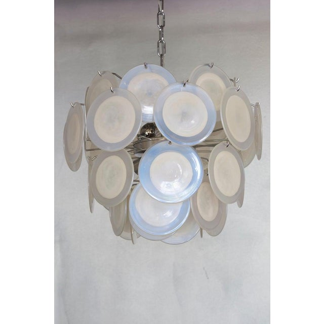 Very nice white iridescent Murano glass disc chandelier attributed to Vistosi. The chandelier is a perfect eyecatcher in...