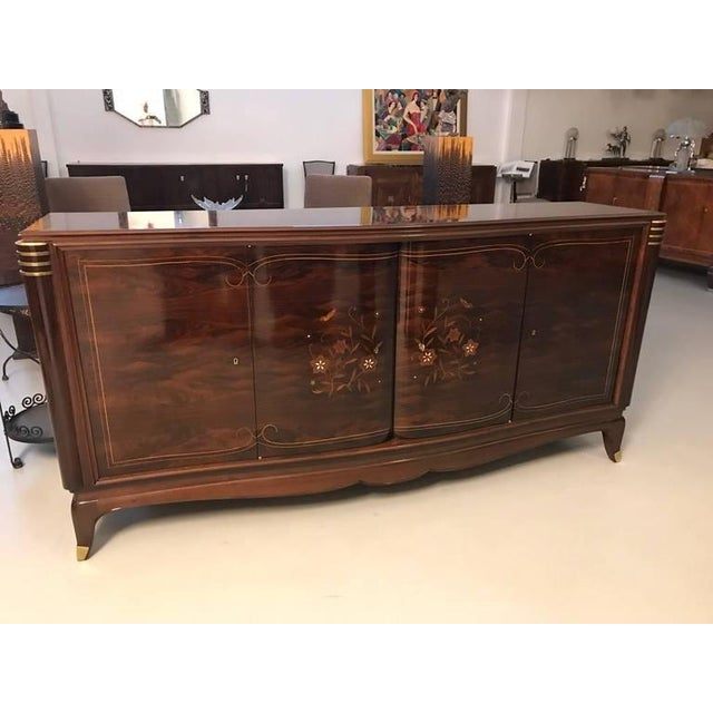 Stunning French Art Deco four-door sideboard in the style of Jules Leleu. With beautiful rosewood and mother-of-pearl...