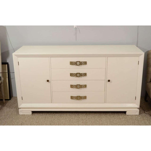 A striking server in cream lacquer with original brass pulls, four drawers bordered by two cabinets for storage, with...