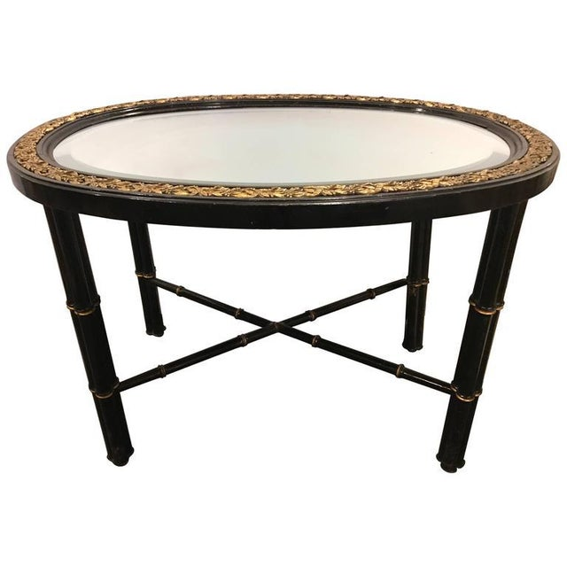 Beveled Mirror Top Black Oval Coffee Table With Bronze Mounts. This fine Hollywood Regency bamboo form coffee table has a...