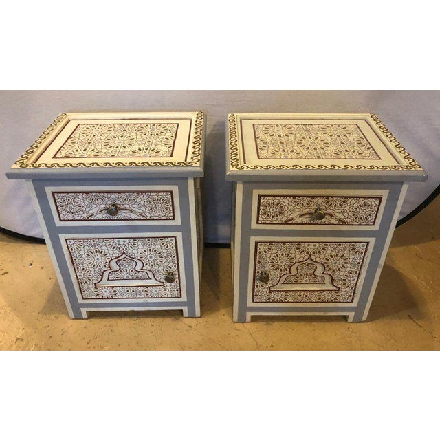 A splendid pair of hand-painted night stand tables with glass top featuring Moorish geometrical design patterns and...