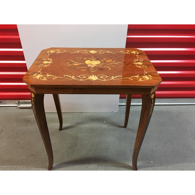 Small Italian inlay table for sale. Beautiful piece, cracking slightly in the lacquer finish. This minor flaw does not...