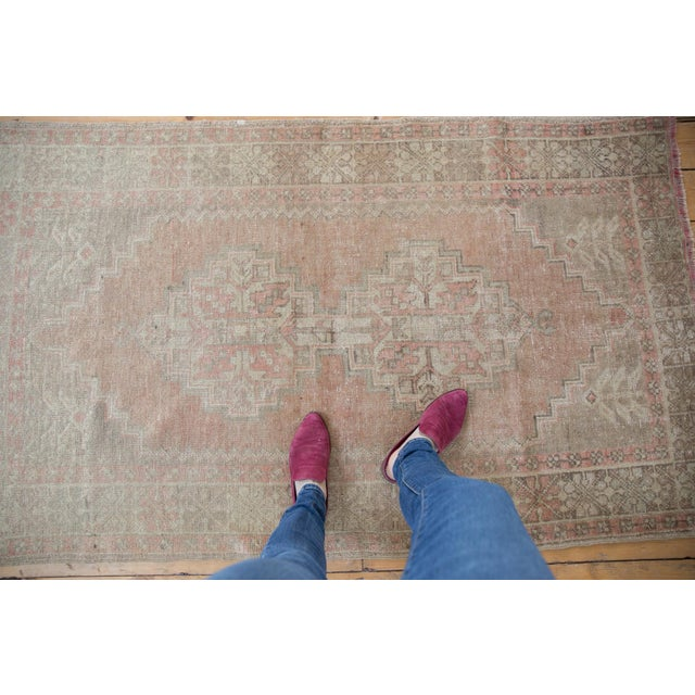 A faded brick rose vintage Oushak rug with a geometric and tribal feel. The corner spandrels feature germinating plants...