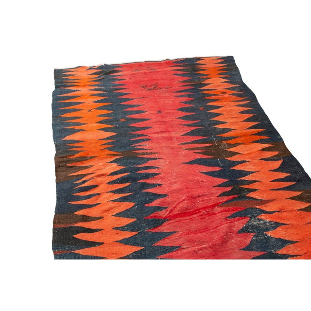 Rug & Kilim runner is lively and fun. A dynamic combination of red and orange pop against the black field. Hand knotted in...