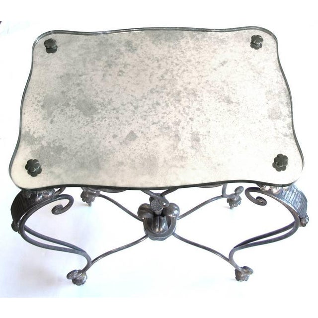 An elegant and stylish French 1940s iron and tole side table with mirrored top; by Rene Drouet; the shaped mirrored top...