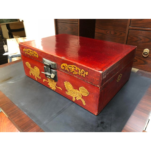 This is an antique Chinese red lacquered coffee box. Gold painted dragons and swirling designs decorate the front of the...