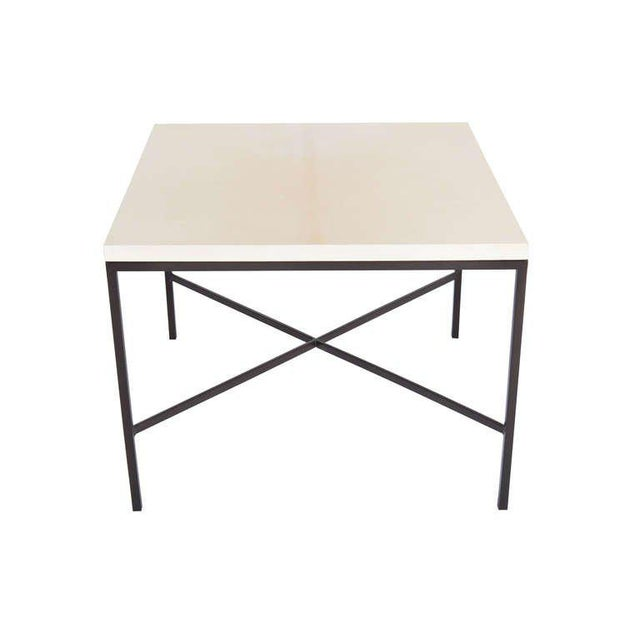 Blackened steel X stretcher Parchment top side table.Half in square stock metal frame with natural parchment wrapped top....