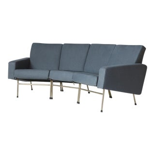 A curved three seat sofa by Pierre Guariche For Sale