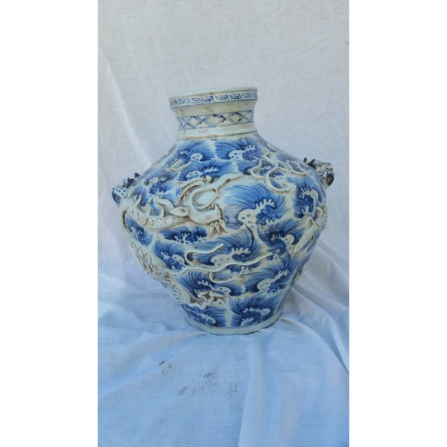 A vintage hand thrown vase with a matte finish rustic glaze. Hand decorated with Chinese dragon relief design.