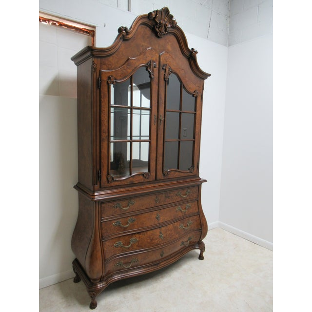 This is a vintage burl wood china cabinet from the 1980s. The piece is in the French provincial style. Door to door...