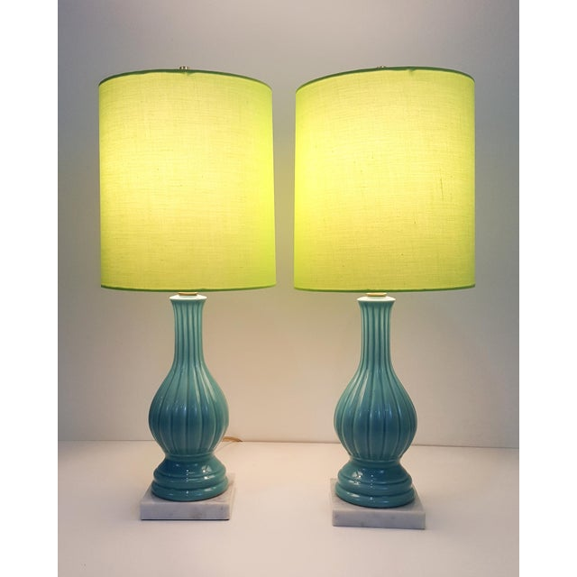 A charming pair of aqua blue glazed pottery lamps with marble bases and topped off with chartreuse shades. The scale of...