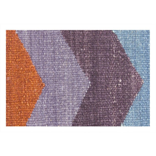 Triangular geometric shapes intersect repeatedly with each other, forming throughout the Kilim Chevron K5 a landscape that...