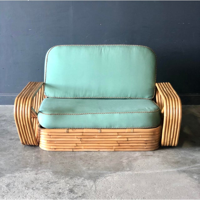 A Paul Frankl Pretzel rattan settee and modular loveseat/pair of chairs. Loose cushions are upholstered in original...
