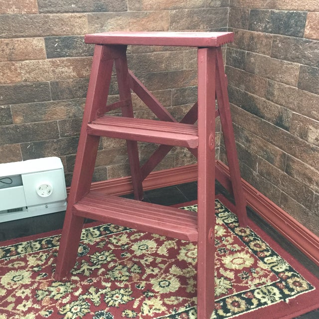 Vintage wooden painted step ladder / stool. Painted in a brick red. All wood with metal hardware that folds closed on the...