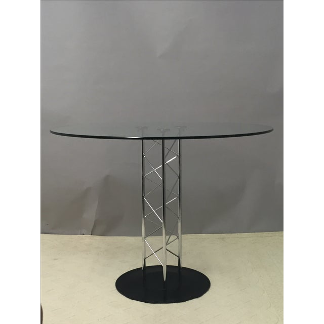 Stylish Mid-Century Modern round table with a sculptural pedestal crafted of zig-zagging chrome rods. Circular black base...
