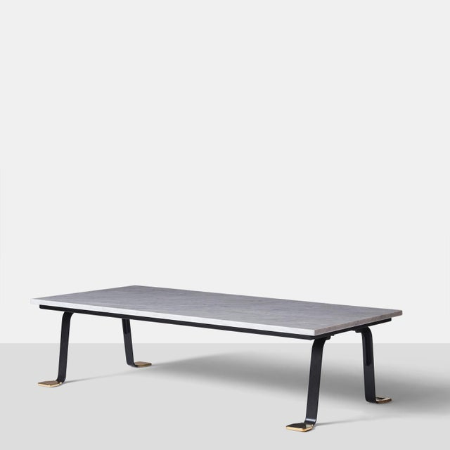 A rectangular coffee table with a Carrara marble top, black metal frame, and polished brass feet. Made in Bolognesi...
