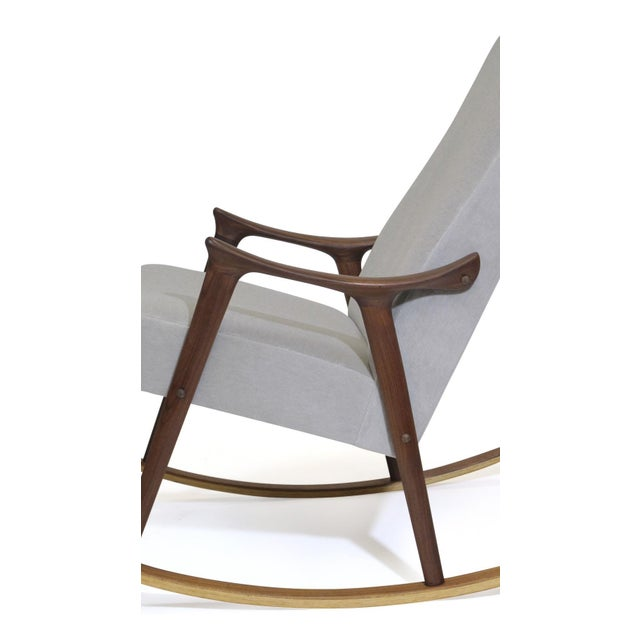 High-back rocking chair designed by Ingmar Relling crafted of a solid teak wood frame with sculpted arms, newly...