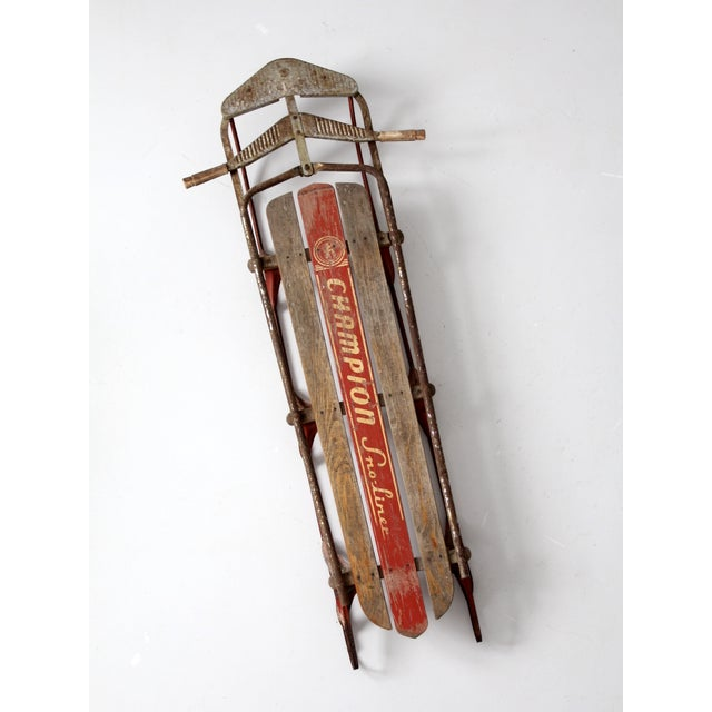 A vintage Champion Sno-Liner sled circa 1950s. The wood and metal sled features a slat board body with steering handles...