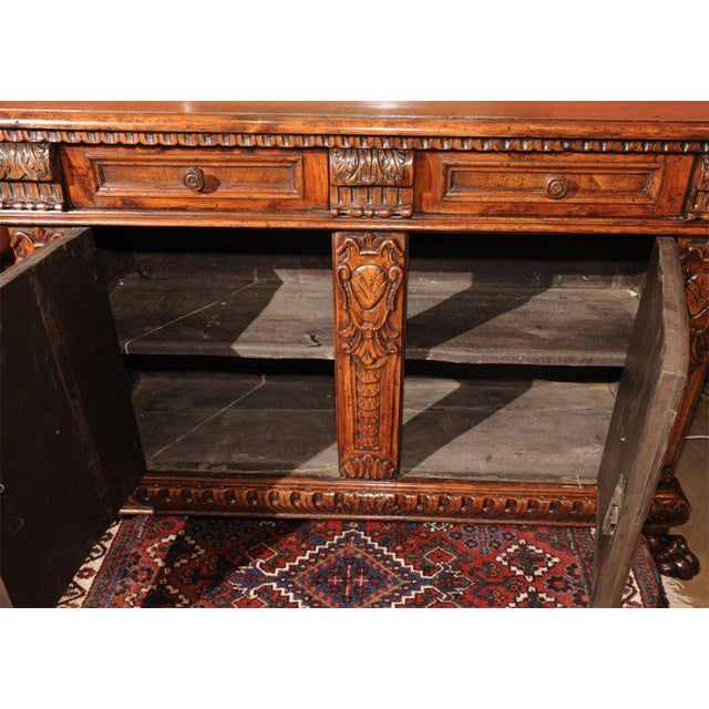 A decorative Baroque Style Italian walnut credenza incorporating 18th century elements remounted in the 19th century.