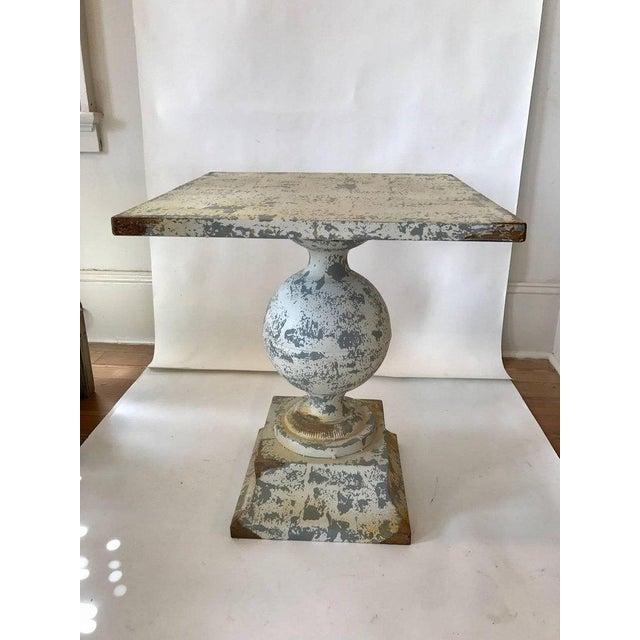 Zinc garden table with bulbous pedestal on square plinth; worn white paint.