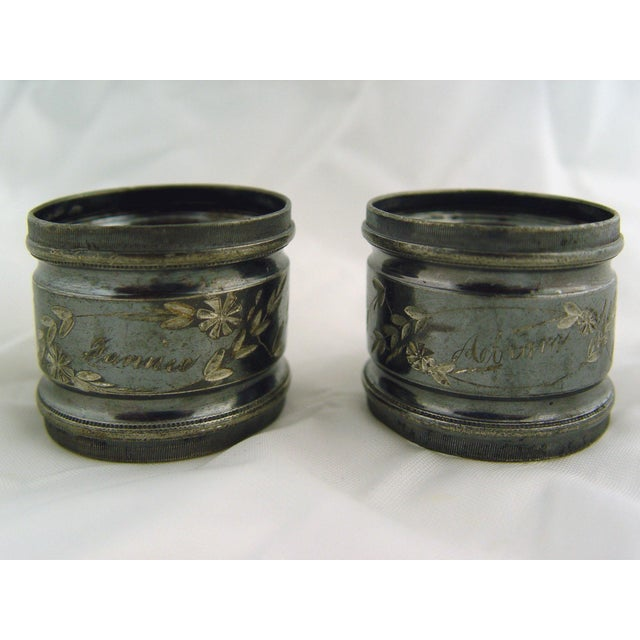 A pair of silver plate napkin rings, engraved floral design with names Fannie and Abram. Produced with a nearly black...