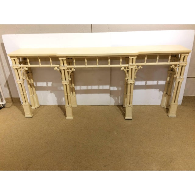 Striking painted wood console table in pale yellow, having glamorous faux bamboo style base and legs.
