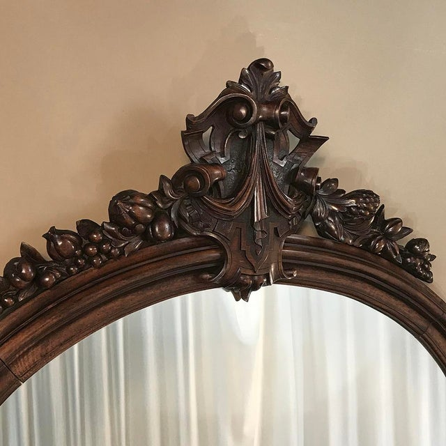19th Century French Louis XVI Walnut Oval Mirror features a tailored frame contrasting with the elaborate crown...