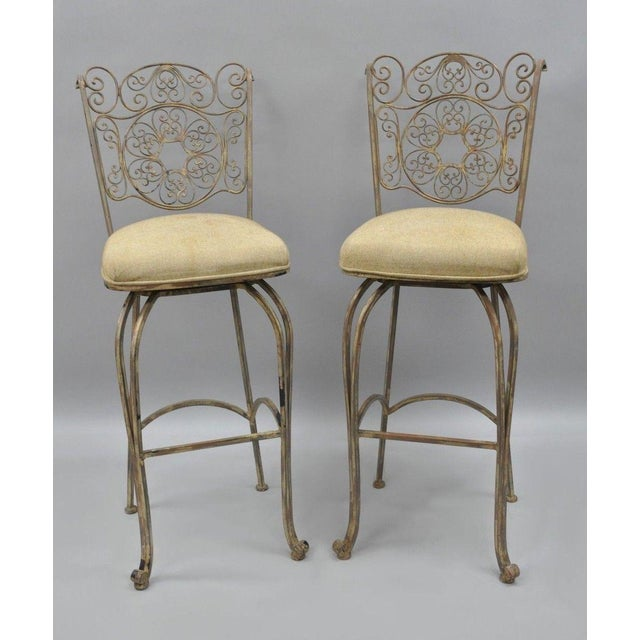 This pair of wrought iron barstools have a distressed finish, fancy scrolling backs and their original labels. Their...