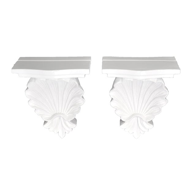 Pair of vintage wall shelves/brackets newly lacquered in white. The shelves have a carved shell motif, plate slots and...
