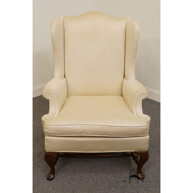 Hickory Chair wingback chair upholstered in a cream color fabric with an amber finish.