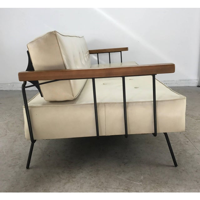 Classic iron and Naugahyde sofa or daybed, wood arms. Wonderful design, back block cushion flips while remaining attached...