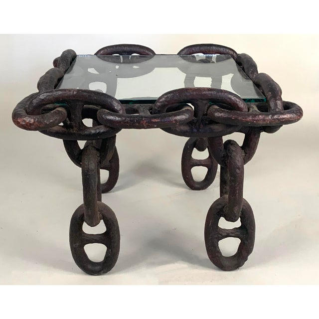 A unique antique 1940s side table or coffee table with the frame made entirely of large link in cast iron, designed to be...